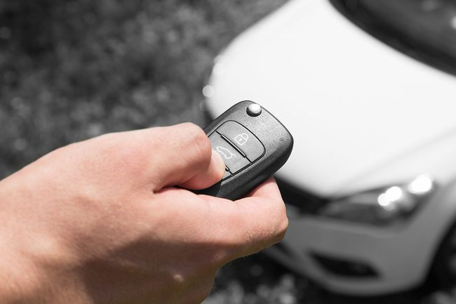 Брелок в руке машина во дворе